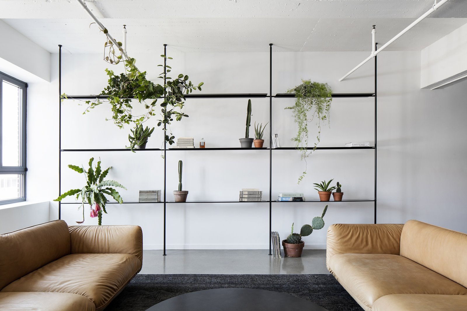 Living Room, Sofa, Bookcase, Shelves, Storage, Concrete Floor, Coffee Tables, and Rug Floor  Saint-Laurent Apartment by Atelier Barda