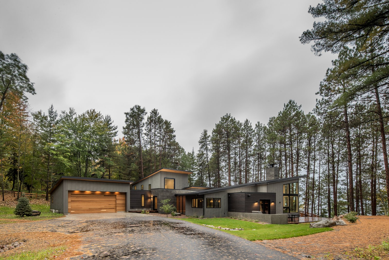 Exterior, House Building Type, Metal Roof Material, Metal Siding Material, Stone Siding Material, Wood Siding Material, Cabin Building Type, Flat RoofLine, and Shed RoofLine  Northern Lake Home by Strand Design