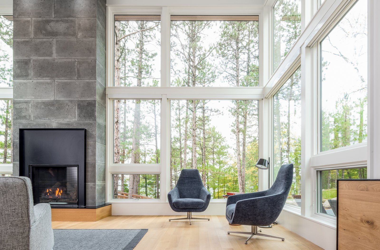 Living Room, Sofa, Chair, Ceiling Lighting, Floor Lighting, Light Hardwood Floor, Standard Layout Fireplace, and Gas Burning Fireplace  Northern Lake Home by Strand Design