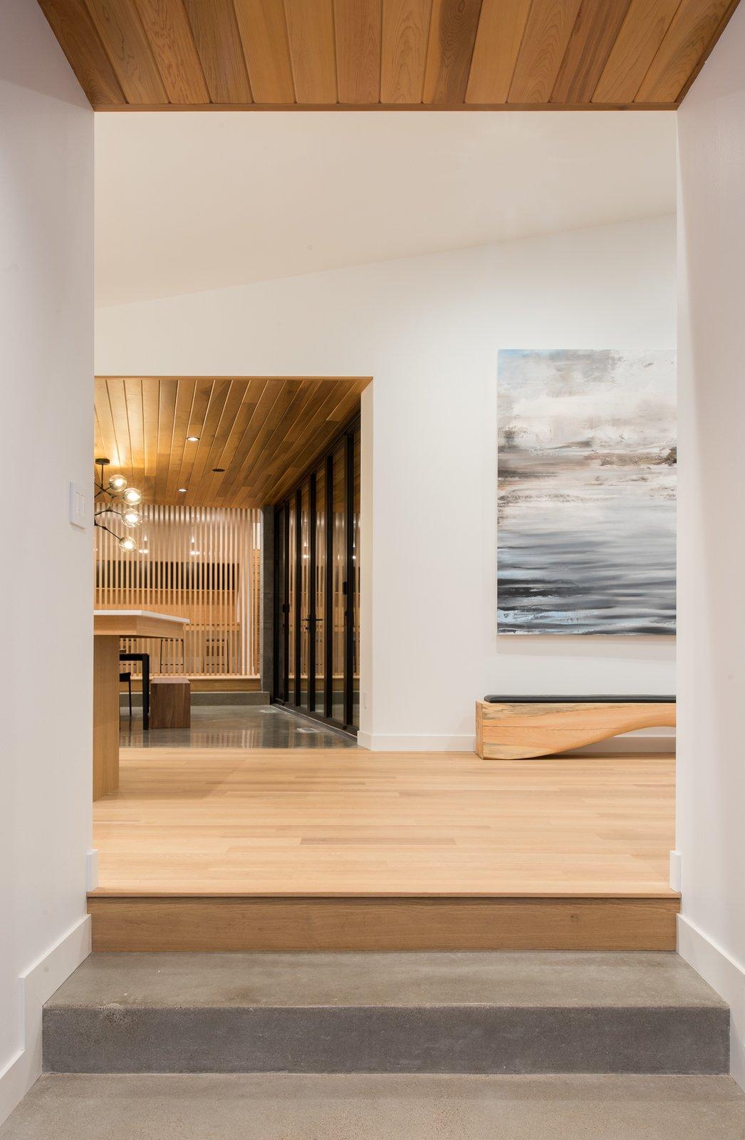 Hallway, Light Hardwood Floor, and Concrete Floor  Northern Lake Home by Strand Design