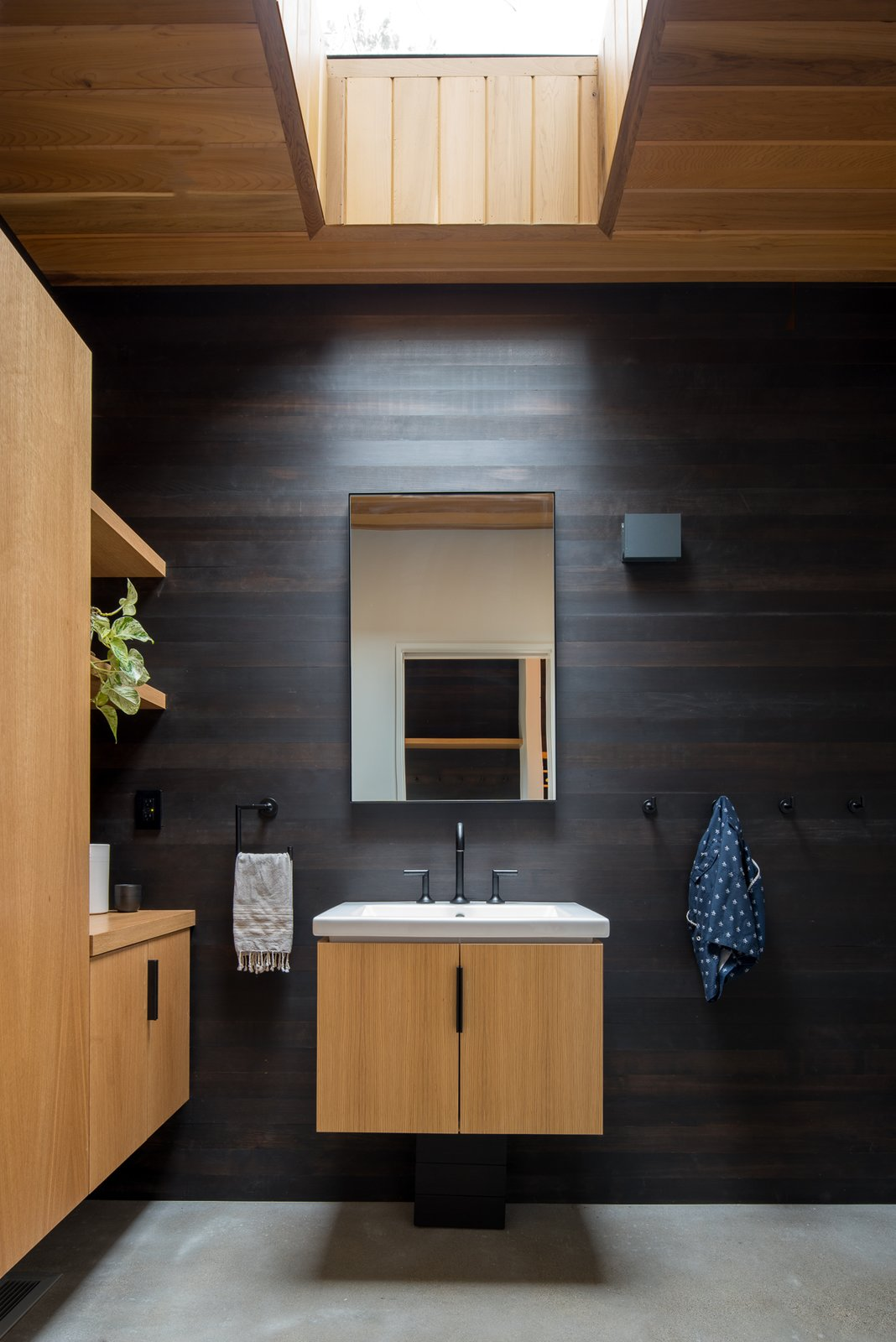 Bath Room, Wood Counter, Concrete Floor, Wall Mount Sink, Ceiling Lighting, and Wall Lighting  Northern Lake Home by Strand Design