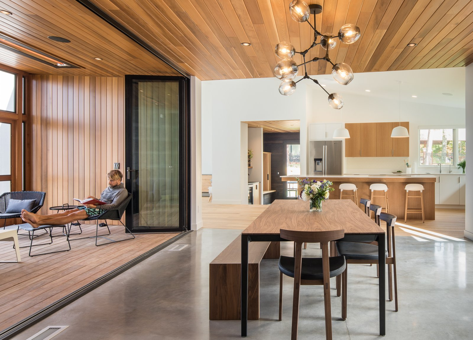Dining Room, Bench, Chair, Pendant Lighting, Light Hardwood Floor, Concrete Floor, Table, and Ceiling Lighting  Northern Lake Home by Strand Design