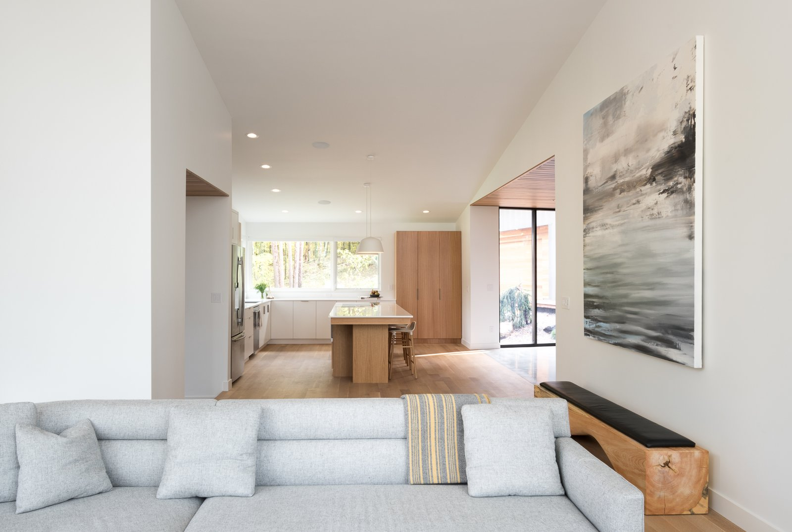 Living Room, Bench, Sofa, Chair, Sectional, Ceiling Lighting, Light Hardwood Floor, and Concrete Floor  Northern Lake Home by Strand Design