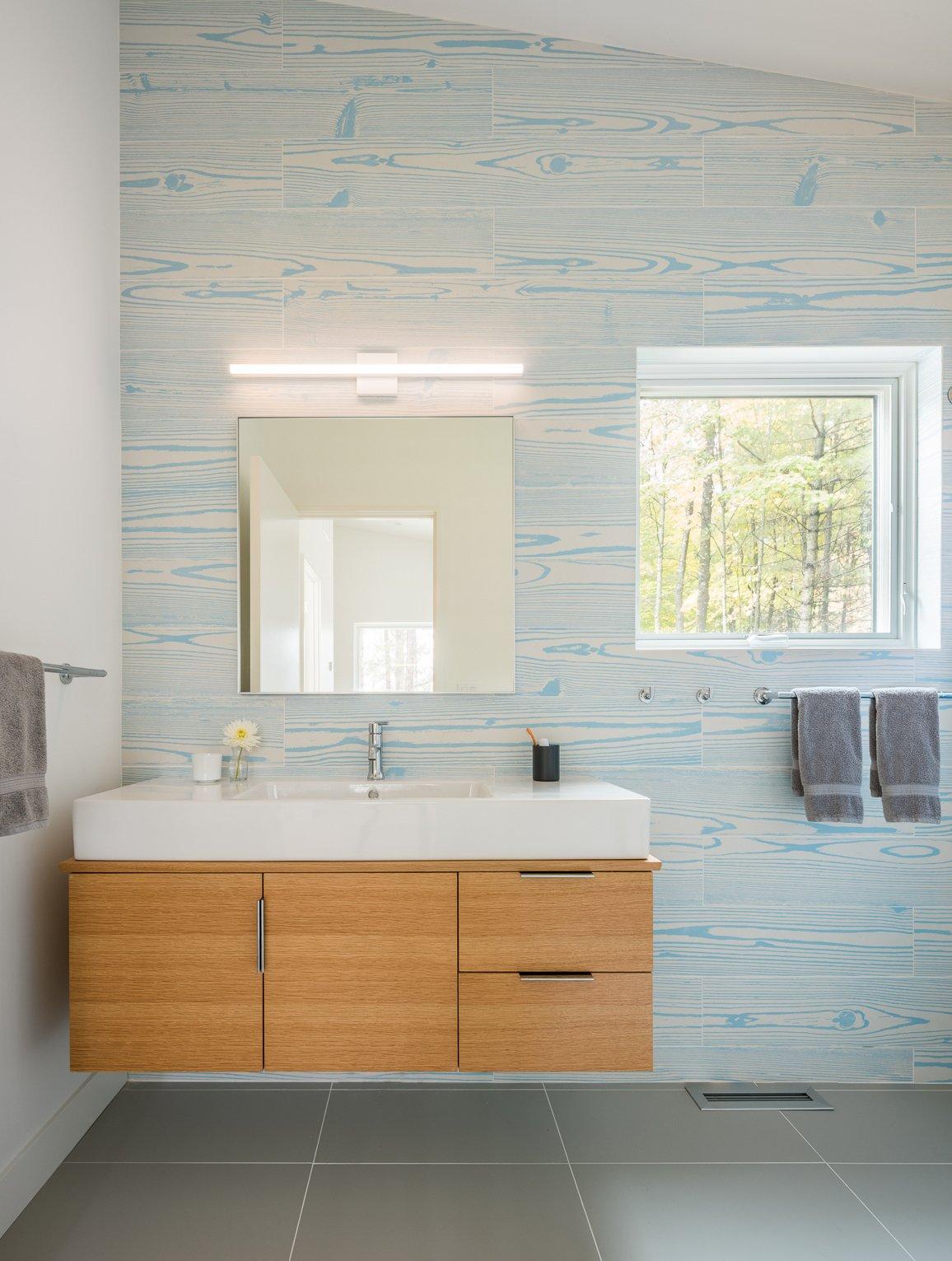 Bath Room, Ceramic Tile Floor, Wall Mount Sink, Ceiling Lighting, Wall Lighting, and Ceramic Tile Wall  Northern Lake Home by Strand Design