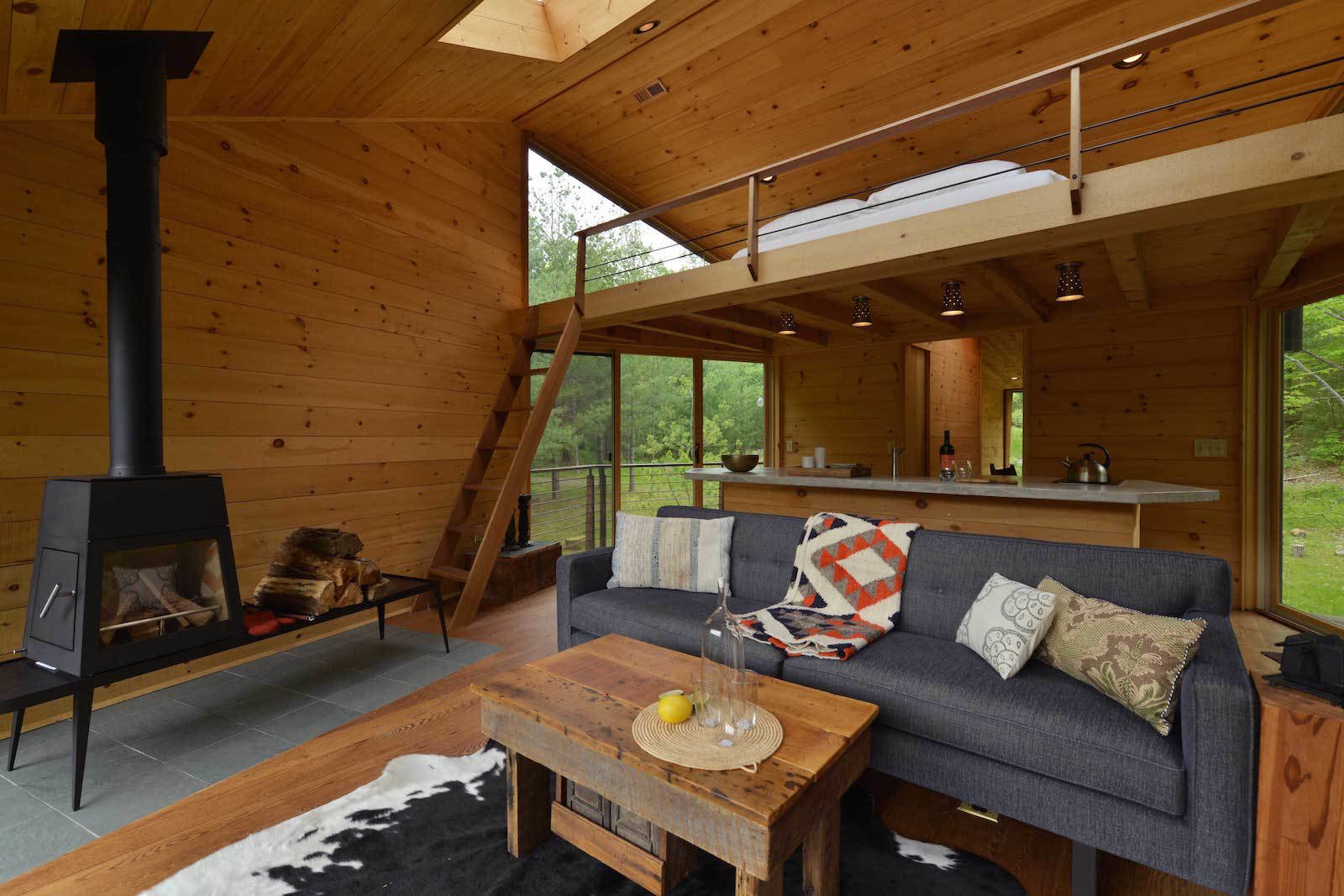 Living Room, Sofa, Recessed Lighting, Ceiling Lighting, Coffee Tables, End Tables, Medium Hardwood Floor, and Wood Burning Fireplace  Photo 4 of 11 in Sleep in This Romantic Tree House Just Outside NYC