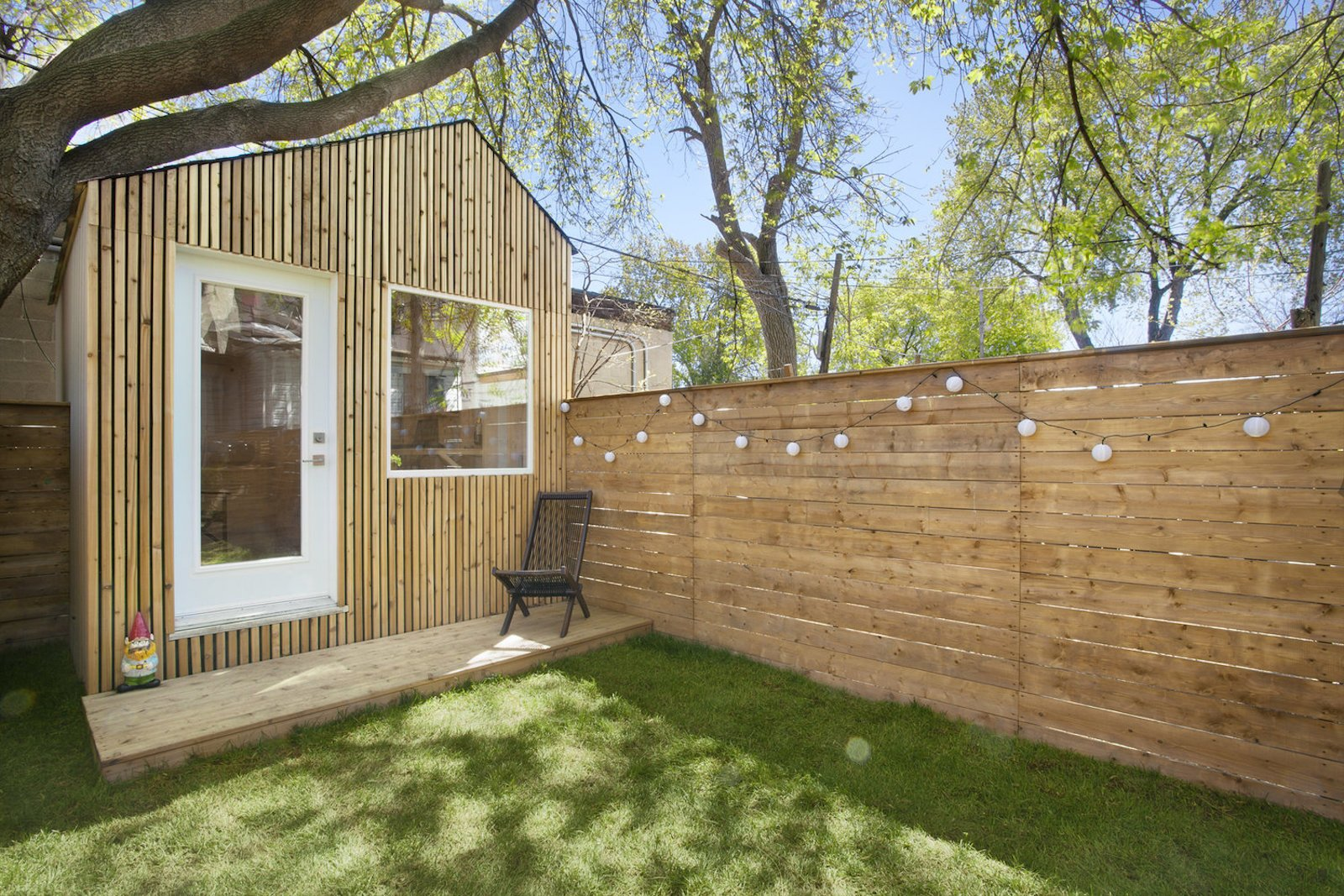 Outdoor, Hanging Lighting, Wood Fences, Wall, Horizontal Fences, Wall, Small Patio, Porch, Deck, Wood Patio, Porch, Deck, Trees, Back Yard, and Grass  Photo 2 of 10 in This Architect's Tiny Studio Is the Ultimate Backyard Workspace