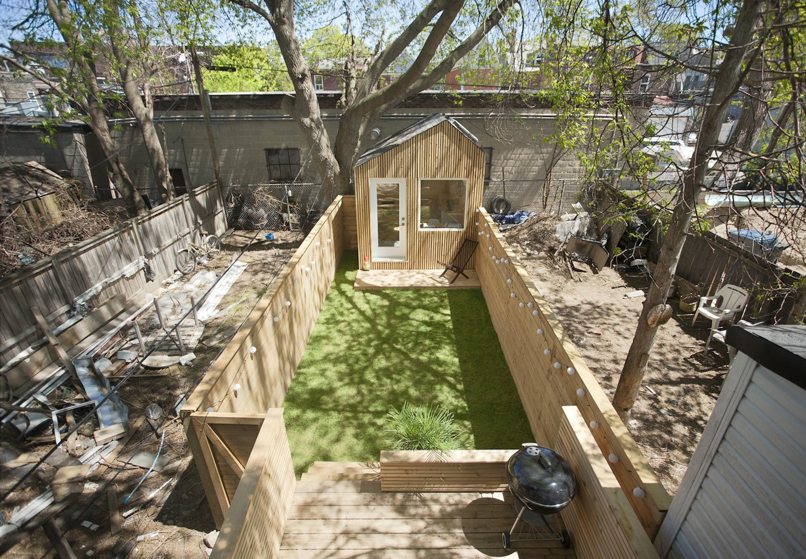 Outdoor, Back Yard, Grass, Trees, Small Patio, Porch, Deck, Wood Patio, Porch, Deck, Decking Patio, Porch, Deck, Horizontal Fences, Wall, Wood Fences, Wall, and Hanging Lighting  Photo 3 of 10 in This Architect's Tiny Studio Is the Ultimate Backyard Workspace