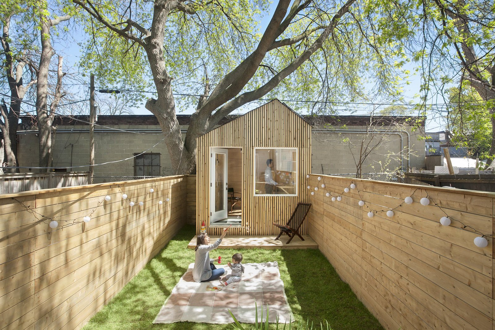 Outdoor, Back Yard, Grass, Trees, Small Patio, Porch, Deck, Wood Patio, Porch, Deck, Horizontal Fences, Wall, Hanging Lighting, and Wood Fences, Wall  Photo 10 of 10 in This Architect's Tiny Studio Is the Ultimate Backyard Workspace