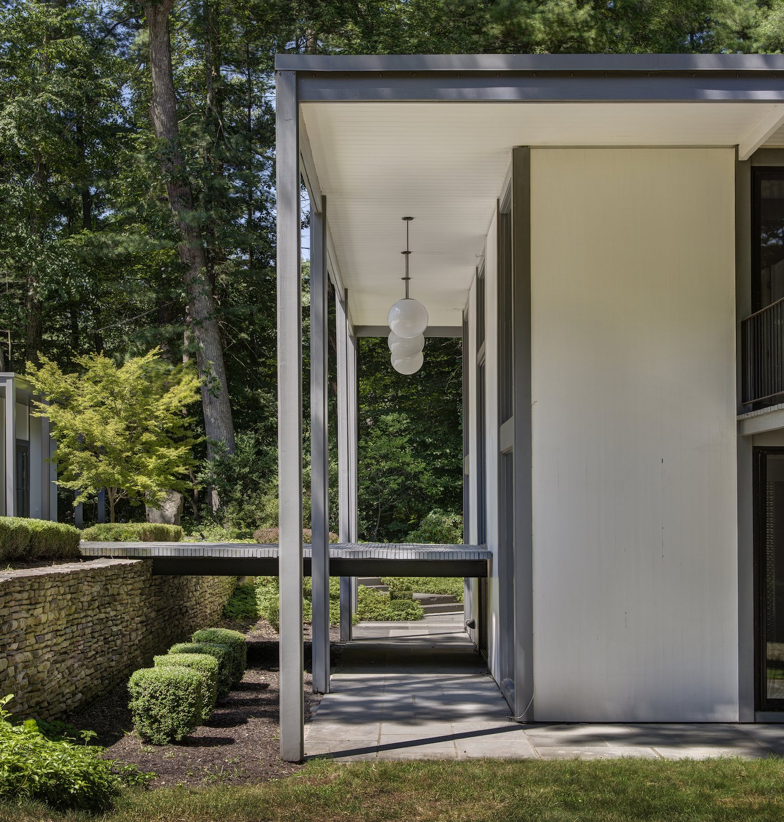Outdoor, Shrubs, Trees, Walkways, Pavers Patio, Porch, Deck, and Stone Fences, Wall  Photo 8 of 13 in A Showstopping Midcentury in New Canaan Hits the Market