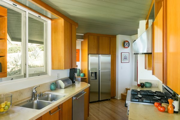 Kitchen, Refrigerator, Dishwasher, Medium Hardwood Floor, Drop In Sink, Wood Cabinet, and Range  Photo 4 of 17 in A Midcentury Schindler Gem With a Writer's Studio Asks $2.3M