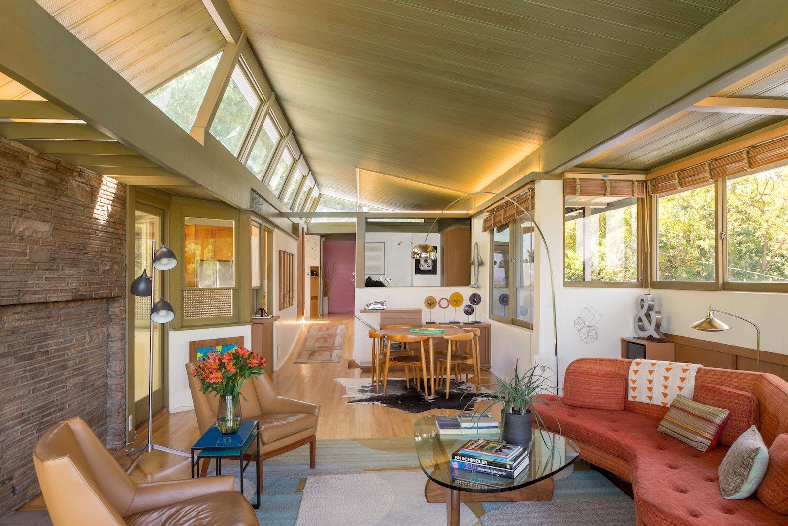 Living Room, Chair, Sofa, Coffee Tables, Floor Lighting, Medium Hardwood Floor, Rug Floor, and Standard Layout Fireplace  Photo 8 of 17 in A Midcentury Schindler Gem With a Writer's Studio Asks $2.3M