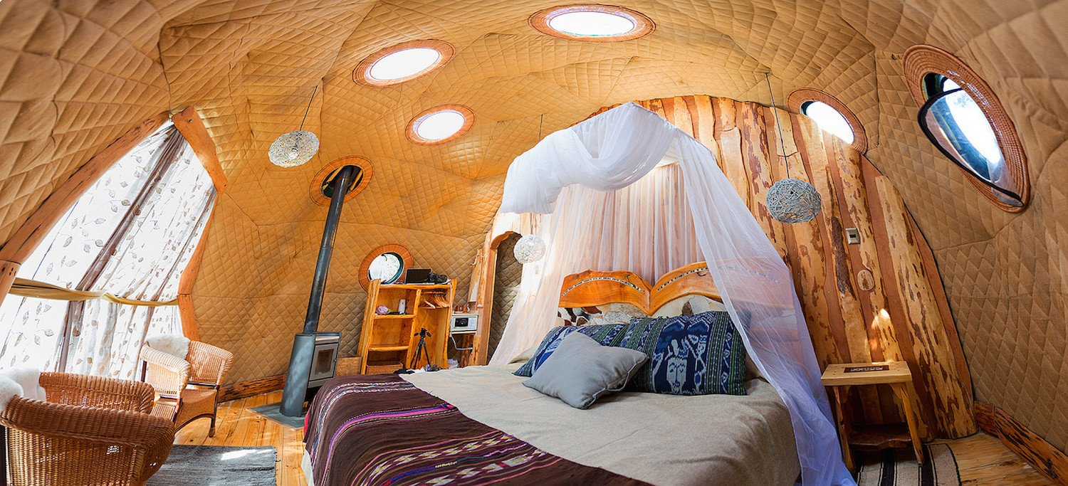 Bedroom, Bookcase, Night Stands, Bed, Pendant, Medium Hardwood, Chair, and Rug  Bedroom Medium Hardwood Pendant Bookcase Photos from Soak Up the Magic of Patagonia at This Eco-Friendly Geodesic Dome Retreat