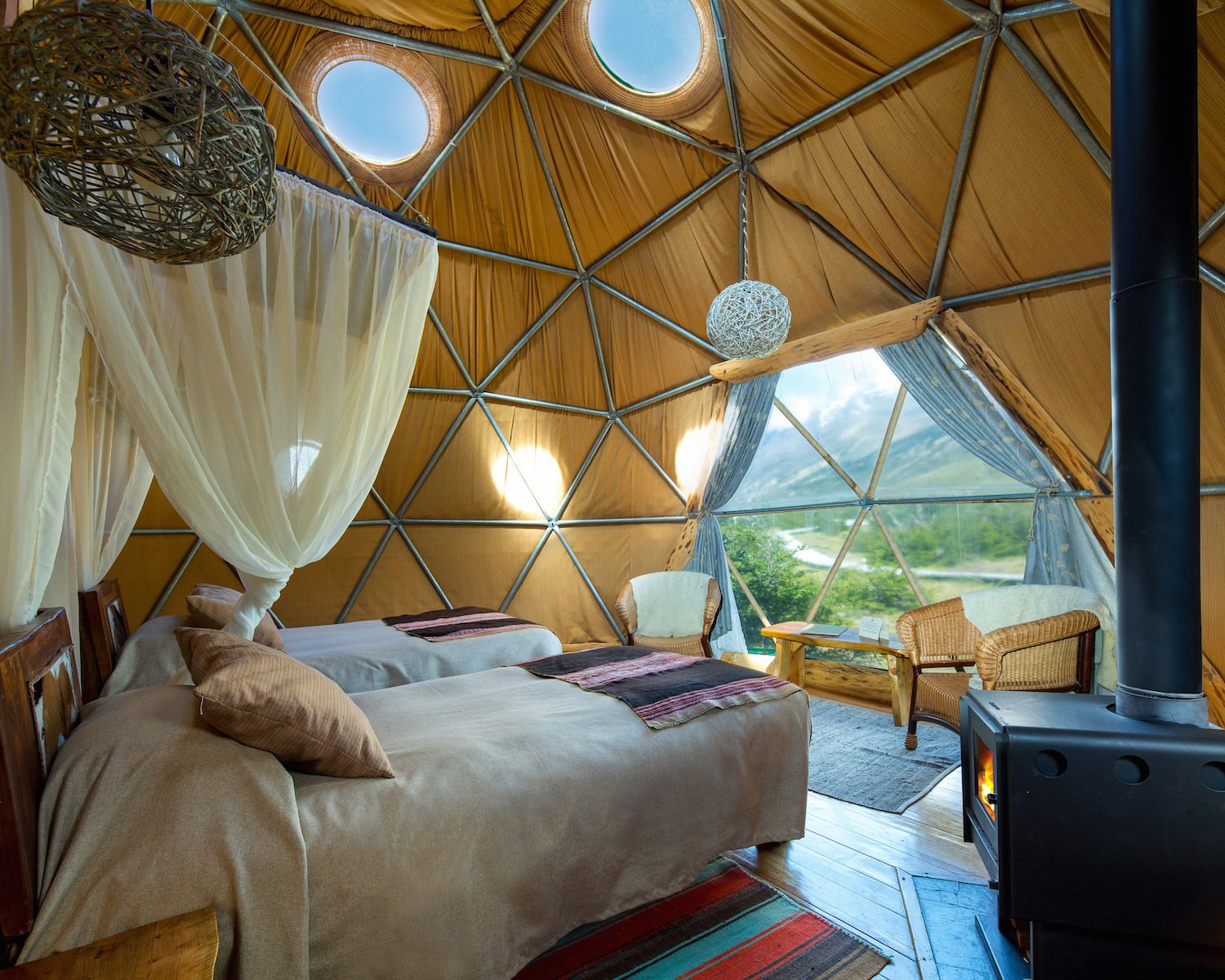 Bedroom, Chair, Pendant Lighting, Bed, Rug Floor, Medium Hardwood Floor, and Night Stands  Photo 4 of 13 in Soak Up the Magic of Patagonia at This Eco-Friendly Geodesic Dome Retreat