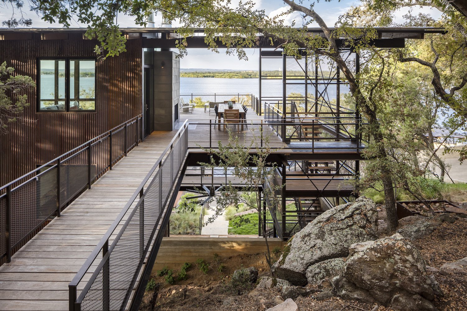 Outdoor, Boulders, Trees, and Wood Patio, Porch, Deck  Photo 7 of 11 in A Spectacular Lakeside Retreat in Texas Embraces the Outdoors