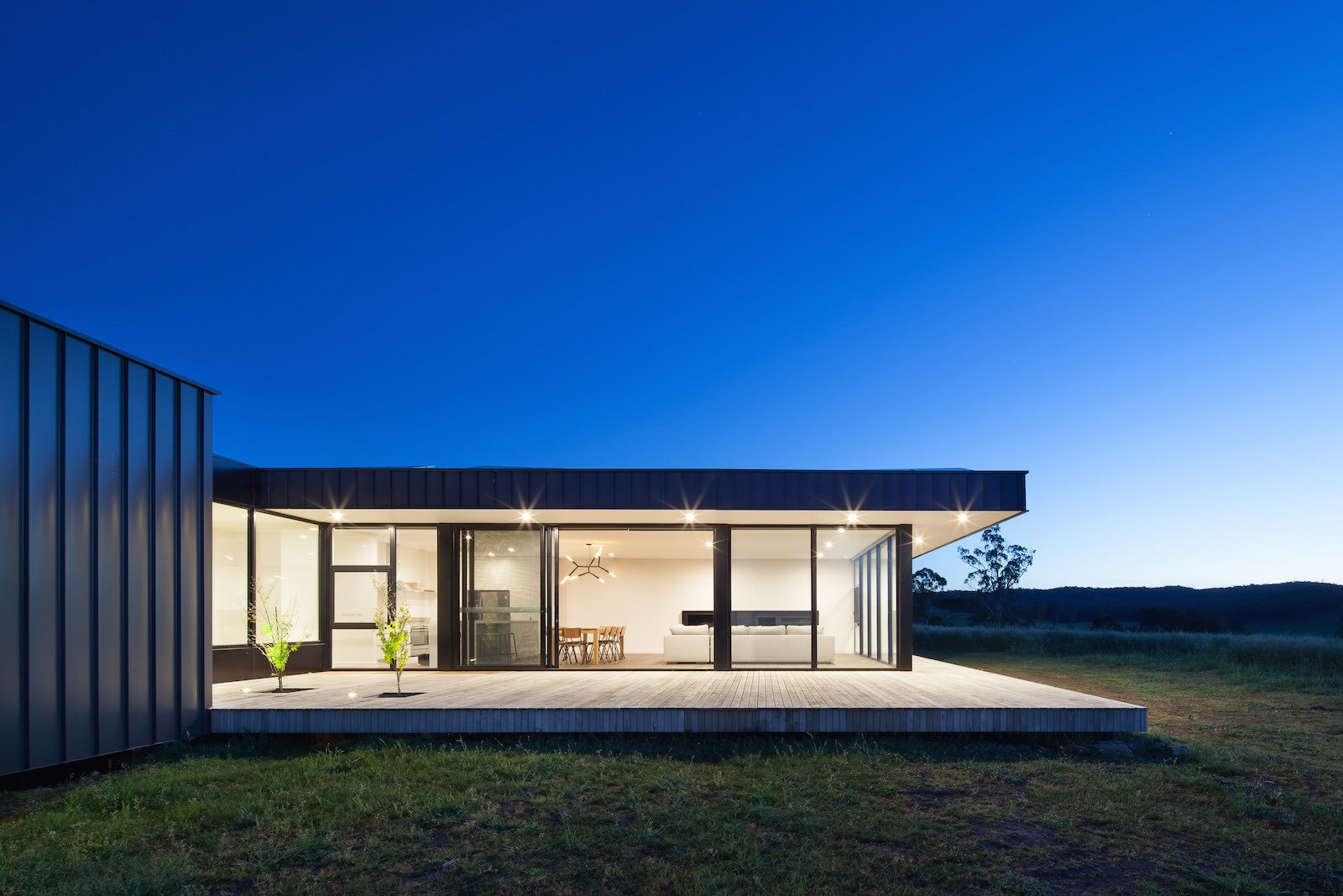 Outdoor, Wood Patio, Porch, Deck, Back Yard, Large Patio, Porch, Deck, and Grass  Photo 6 of 10 in Two Families Embrace Off-Grid Living in This Sustainable Prefab Home