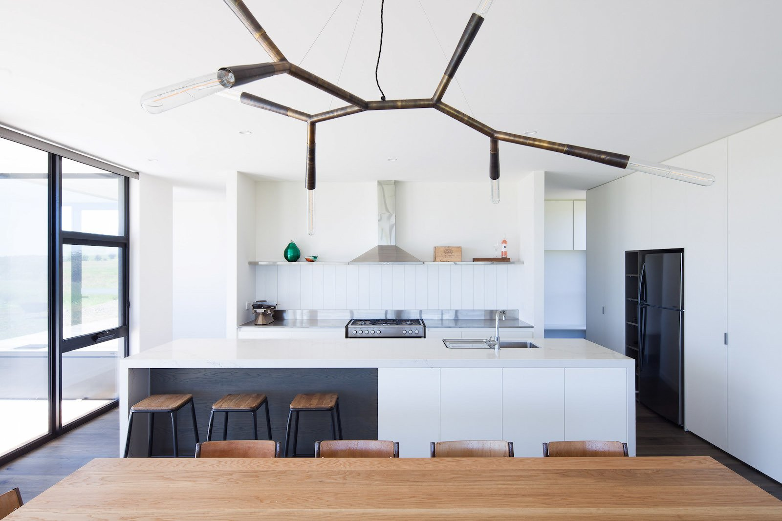Dining Room, Pendant Lighting, Dark Hardwood Floor, Chair, and Table  Photo 7 of 10 in Two Families Embrace Off-Grid Living in This Sustainable Prefab Home