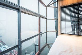 This top-level bedroom boasts spectacular views, thanks to the fully glazed walls and floor-to-ceiling windows.