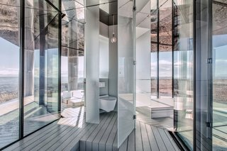 Go Stargazing in This Off-Grid Glass Prefab Nestled in the Desert - Photo 9 of 13 - The bathroom is concealed behind a slim door.