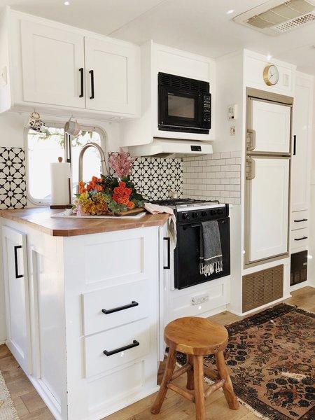 The compact kitchen features a ceramic tile backsplash.