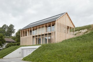 To help blend the building into the landscape, the sections of the home visible above the slope are cladded in natural and unfinished spruce sourced from the owner's own forest.