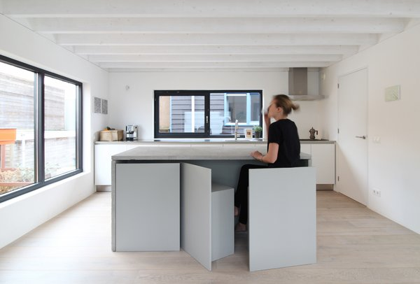 An Architect Creates a Two-Level Houseboat For His Family on a Tight Budget - Photo 1 of 10 - Built-in storage and space-saving furnishings—such as seating that stores flush beneath a table—reduce visual clutter without compromising functionality.