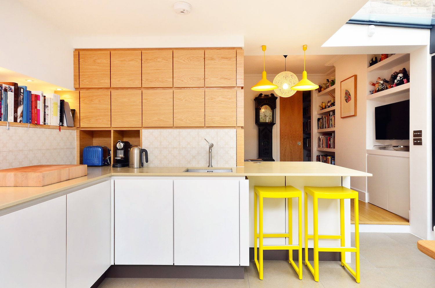 Bright yellow Torch S3 large cone pendant lights and Seleri bar stools reinforce the black-and-yellow color palette.