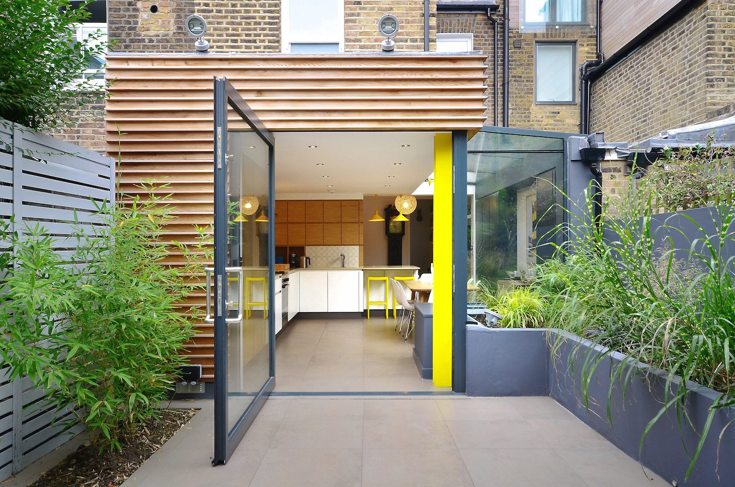 The kitchen's structural pillar was painted a vibrant yellow, a shade that's echoed in the furnishings.