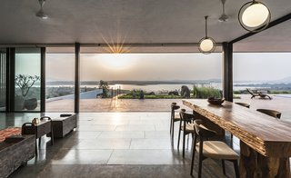The open-plan dining and living area flow seamlessly into the outdoor terracotta terrace.