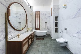 A luxurious bathroom with marble walls and earthy timber elements.