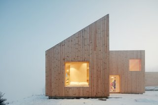 Planning regulations required a gable roof, which the architects split into four shed roofs carefully designed to respond to heavy snow and meet spatial and aesthetic wishes.