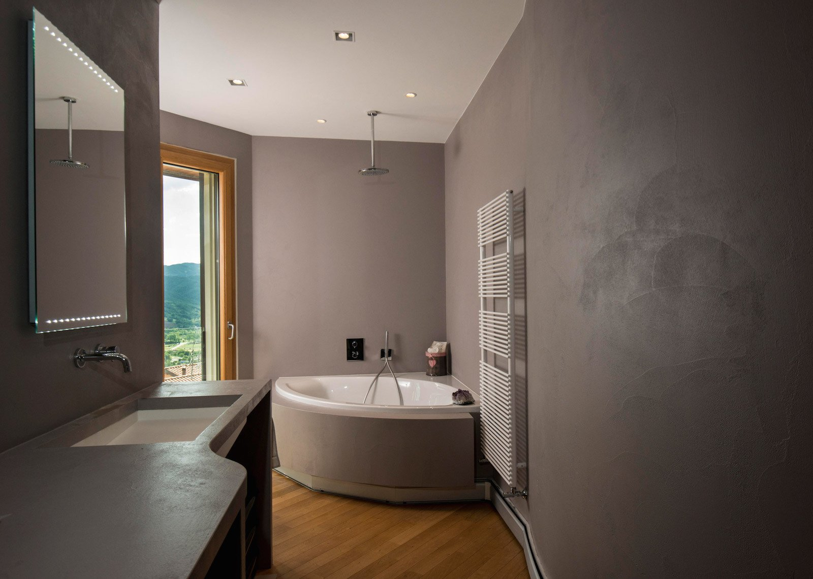 Bath Room, Medium Hardwood Floor, Alcove Tub, Concrete Counter, Recessed Lighting, and Undermount Sink Views of the countryside can be enjoyed from the bathtub.  Photo 7 of 8 in This Octagonal Prefab in Italy Rotates a Full 360 Degrees to Follow the Sun