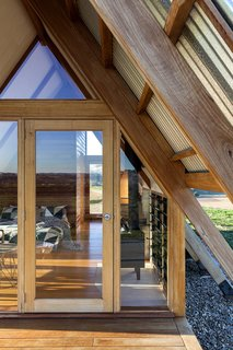 The glazed door, along with other openings, allow guests to enjoy sunset views from bed.