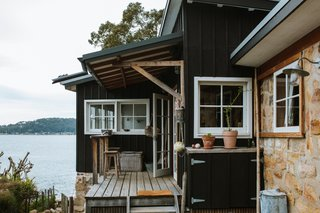 Jamie and Ingrid stained the timber facade a dark blackish-brown to blend the shack into the landscape, but kept the window frames white for a stark pop of contrast.