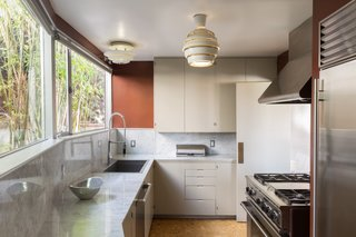 The kitchen features cork flooring and an Alvar Aalto Beehive pendant lamp.