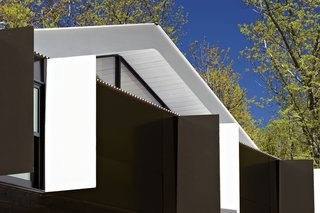 The roof overhang is painted white to bounce more light indoors.