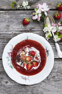 A pudding of an assortment of locally foraged summer strawberries served with cream.