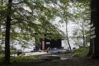 Blackened timber clads the boathouse.