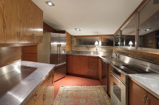Stainless steel countertops, provided from the homeowner's business, Flour City Ornamental Iron Company, has replaced the linoleum countertops specified by Wright.
