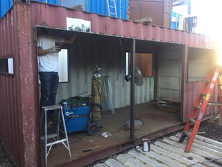A before image of the used shipping container during the initial phases of its transformation.