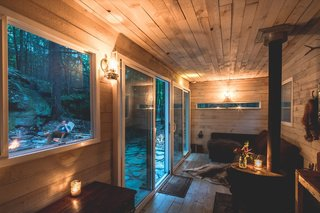 The glazed doors and windows were placed on opposite sides of the cabin to maximize light and transparency, as well as to optimize views of the outdoors.