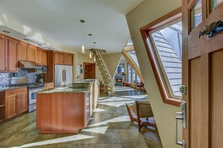 The kitchen has timber cabinetry, granite countertops, and ceramic tile flooring.