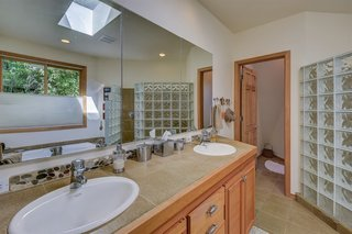 A peek inside the master bathroom with a double vanity and glass block shower.