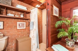 The master bathroom boasts an exposed brick wall.