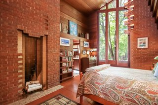 The master bedroom includes a brick fireplace, a 25-foot-tall ceiling, and doors that lead outside.