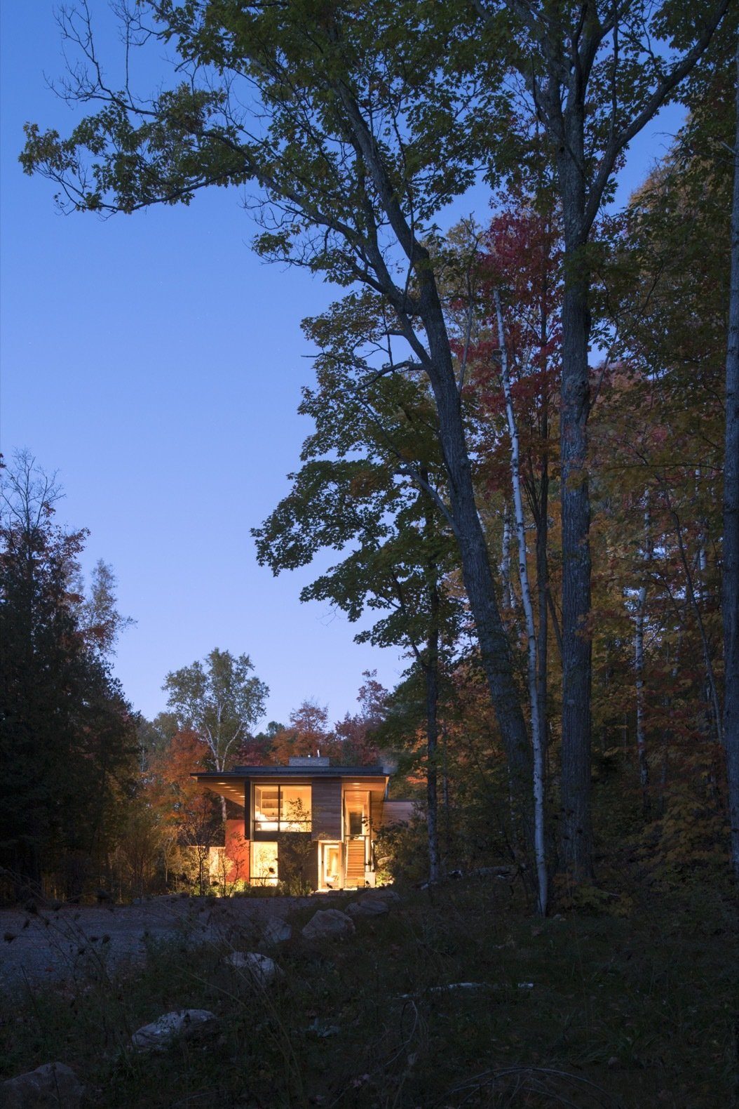 Exterior, Cabin Building Type, House Building Type, Glass Siding Material, Metal Roof Material, Wood Siding Material, Concrete Siding Material, and Flat RoofLine The house was strategically placed between the lake and an adjacent granite rock-face to capture key landscape views.    Photo 2 of 16 in This Award-Winning Cabin Is a Relaxing Antidote to City Living