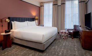 The Publisher's Suite also enjoys views of Magazine Street below. All rooms are furnished with ink-colored leather headboards, accent furnishings from Bryan Ashley, floral patterns, and brass and walnut accents throughout.