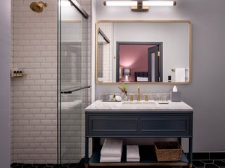 The elegant bathrooms are finished with white beveled subway tile, marble countertops, and brass Kohler fixtures.