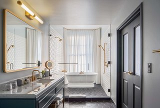 The luxurious Publisher Suite bath features a free-standing bathtub next to a large window with a privacy curtain.