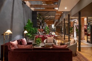 The 60-foot-high atrium floods the lobby and Press Room bar with natural light, while lush plantings and a Havwoods parquet flooring soften the original exposed and slate-colored plaster walls.