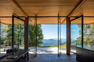 A spectacular southeast-facing view greets guests in the great room. Full-height Fleetwood glazed doors pivot open to connect the living spaces with nature outside.